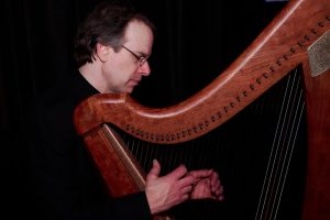 a man playing a wire strung harp against a dark background
